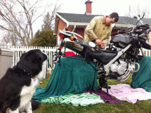 working on servicing motorcycle in backyard